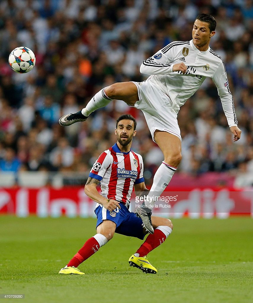 Cristiano Ronaldo (R) of Real Madrid and Jesus Gamez of Atletico de Madrid compete for the ball during the UEFA Champions League Quarter Final second leg match between Real Madrid CF and Club Atletico de Madrid at Estadio Santiago Bernabeu on April 22, 2015 in Madrid, Spain.