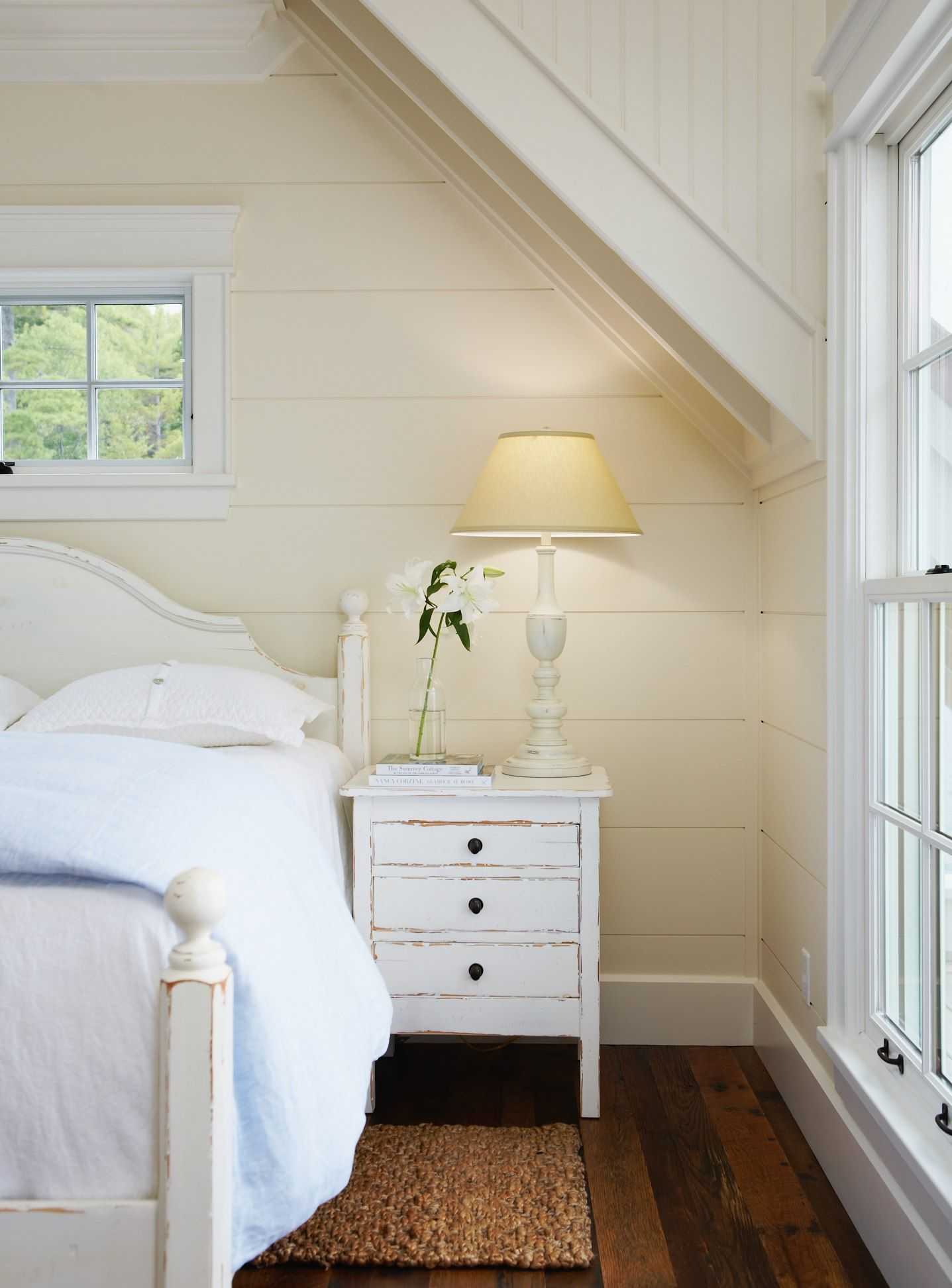 White bedside table with drawers jute or similar rug beside bed to
