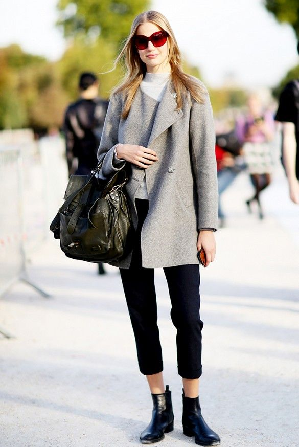 Cropped black pants and ankle boots pair well with a gray overcoat.