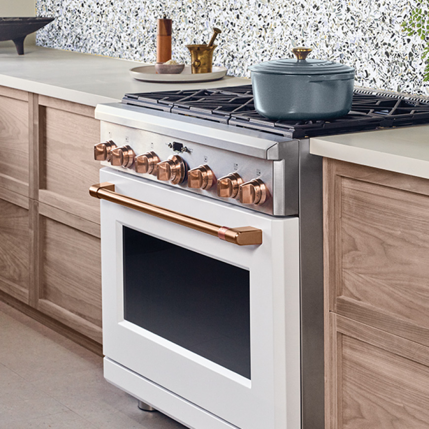 An Enamel Pot Sits On A Matte White Cafe Range With Brushed Copper Trim The Stylish Copp In 2020 Professional Kitchen Appliances Kitchen Appliances Ge Cafe Appliances
