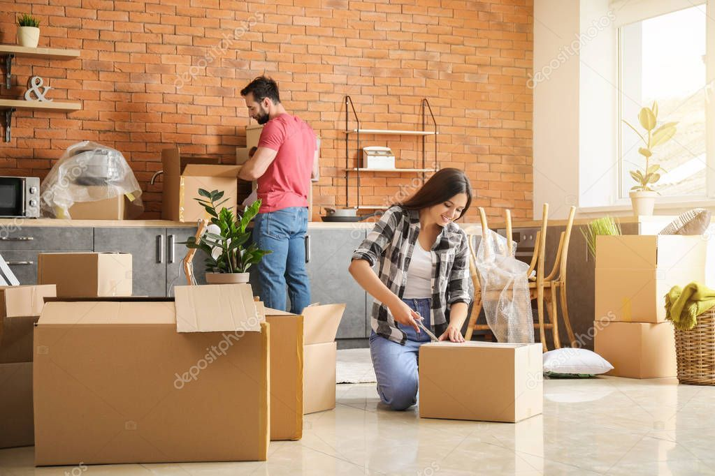 Young Couple Unpacking Things After Moving Into New House Stock