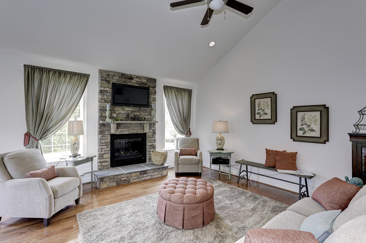 Model Home Curtains cute cozy sitting area with stone fireplace, high vaulted ceiling