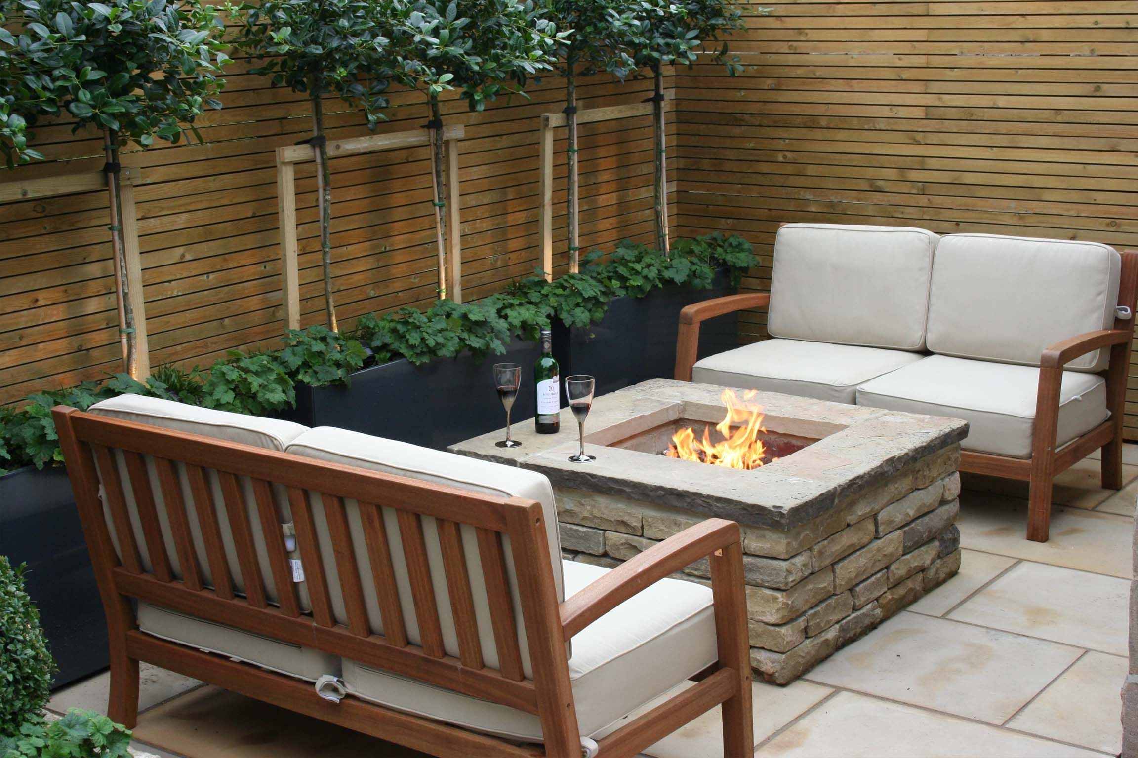 Urban chic courtyard garden outdoor fire pit outdoor sofas bestall co evergreen planting sawn stone