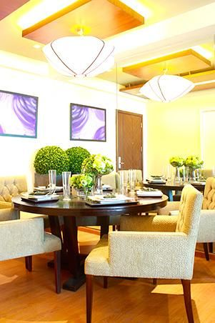 In the dining area, the floor and ceiling have been left bright to emphasize the home's airiness. The ceiling is also adorned with overhead lighting fixtures to make the space seem more open. The dining table is an old piece from the interior designer's family home.