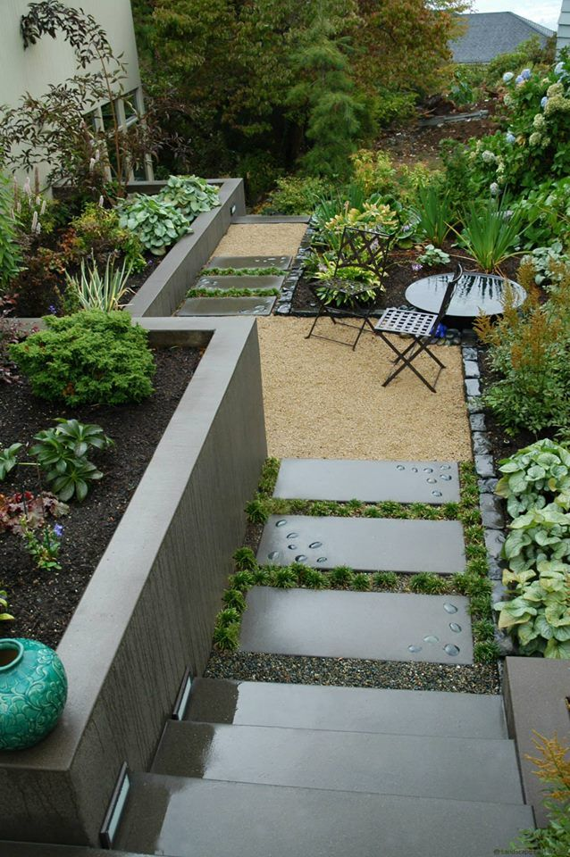 This Smaller Backyard Is Landscaped To Maximize E Includes An Acid Etched Concrete Retaining Wall Gravel Patio More