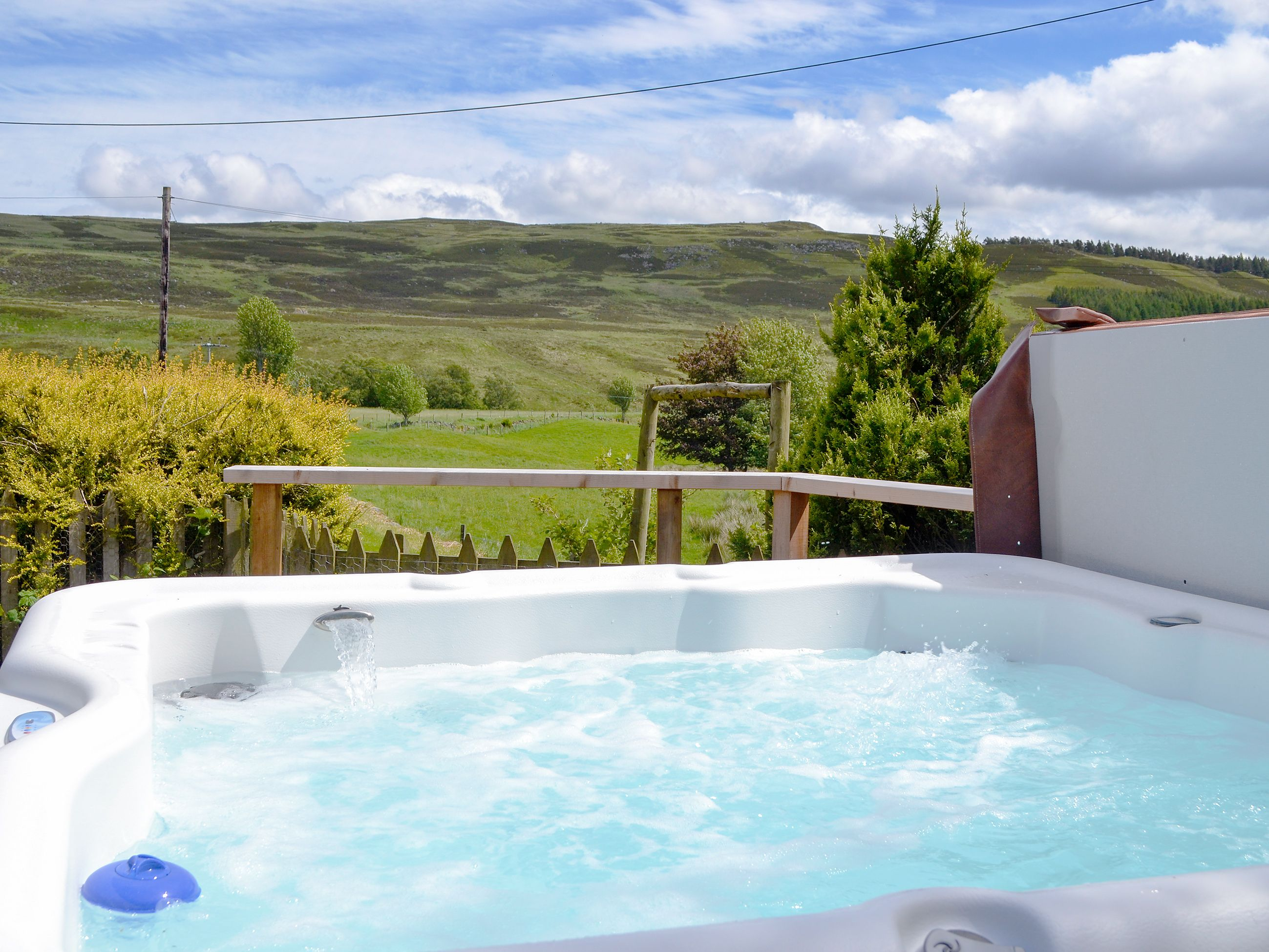 Soak in the gloriously beautiful landscape from the private hot tub ...