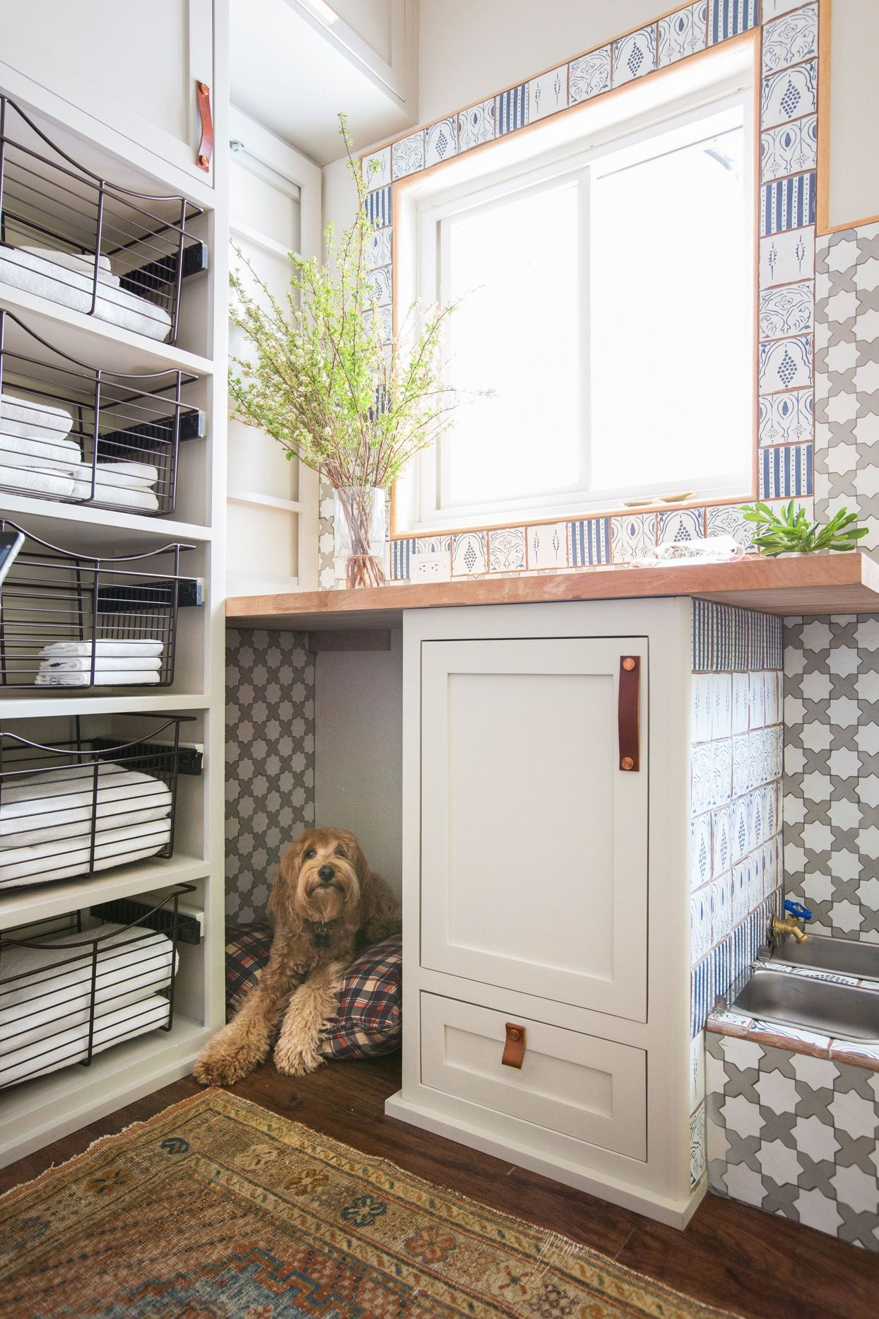 All family members want privacy from time to time, and you can provide your pet that same luxury with a space of their own. Tuck a pet bed under shelves or in small nooks to keep it out of heavy traffic zones and offer pets someplace quiet and secure to rest. #petstorageideas #storageandorganizationideas #petsuppliesorganization #dog #cat #petparent #bhg