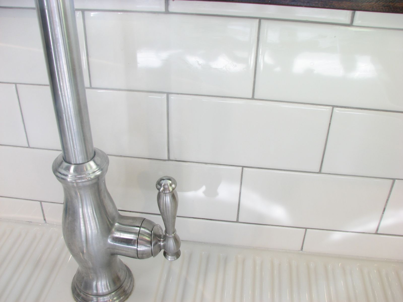 subway tile with silver grout and white caulking along bottom