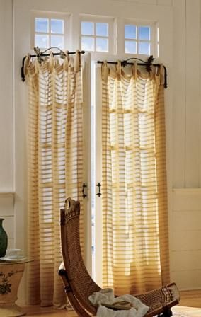 a swinging-arm curtain rod provides a clever solution to draping a