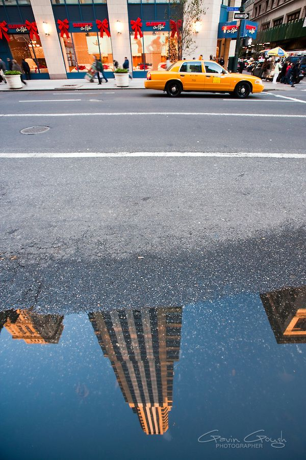 Skyscrapers reflecting in a puddle of Fifth Avenue as a yellow cab waits at traffic lights