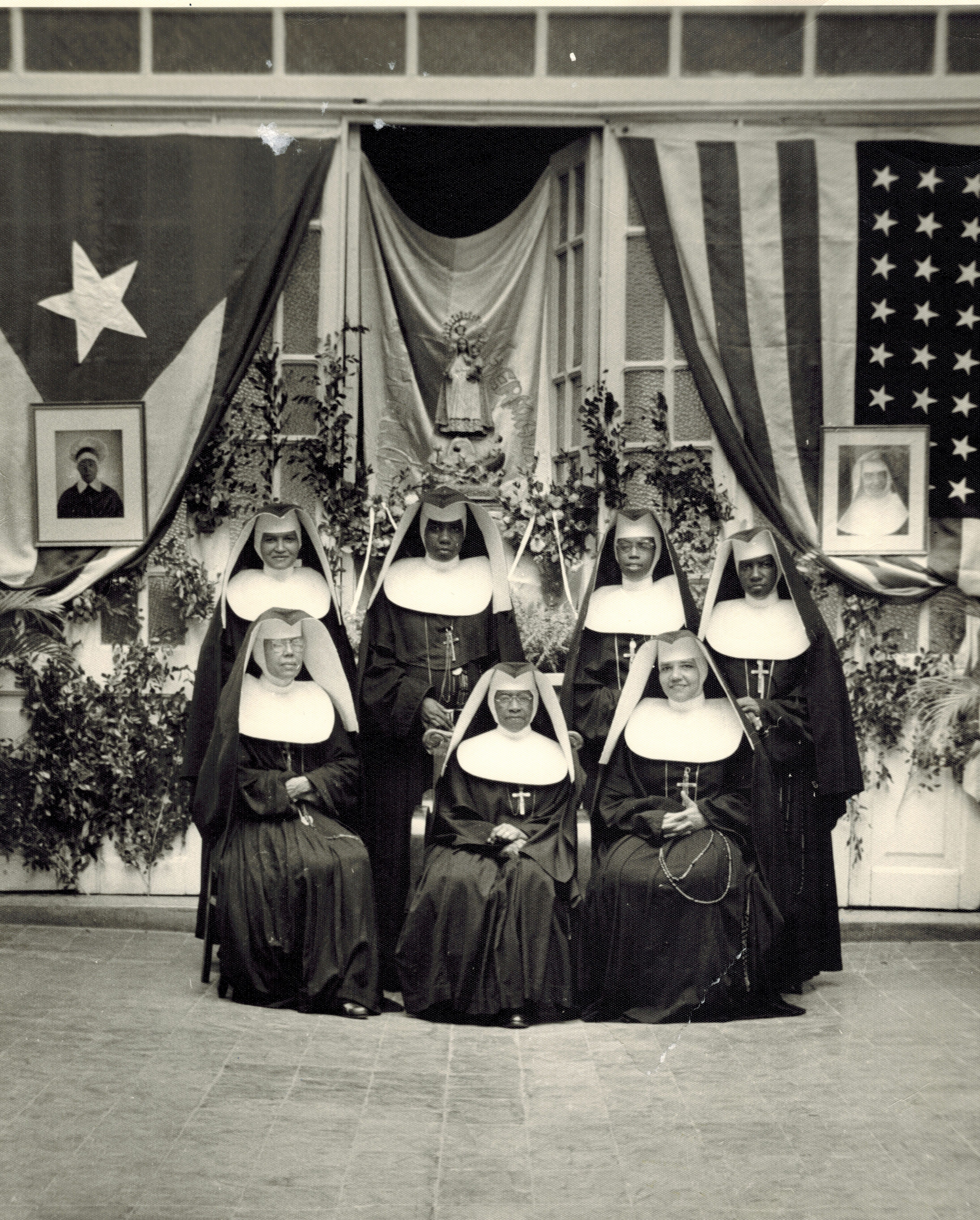 1954 photo of Sisters Margarita, Carmen, Maris Stella, Henrietta, Emmanuel, Teresa [Superior General at the time] & Zoila @ Our Lady of Charity in Havana.  On the left is a picture of Mother Lange in front of the Cuban flag, while on the right is a picture of Mother Consuella Clifford in front of the American flag.