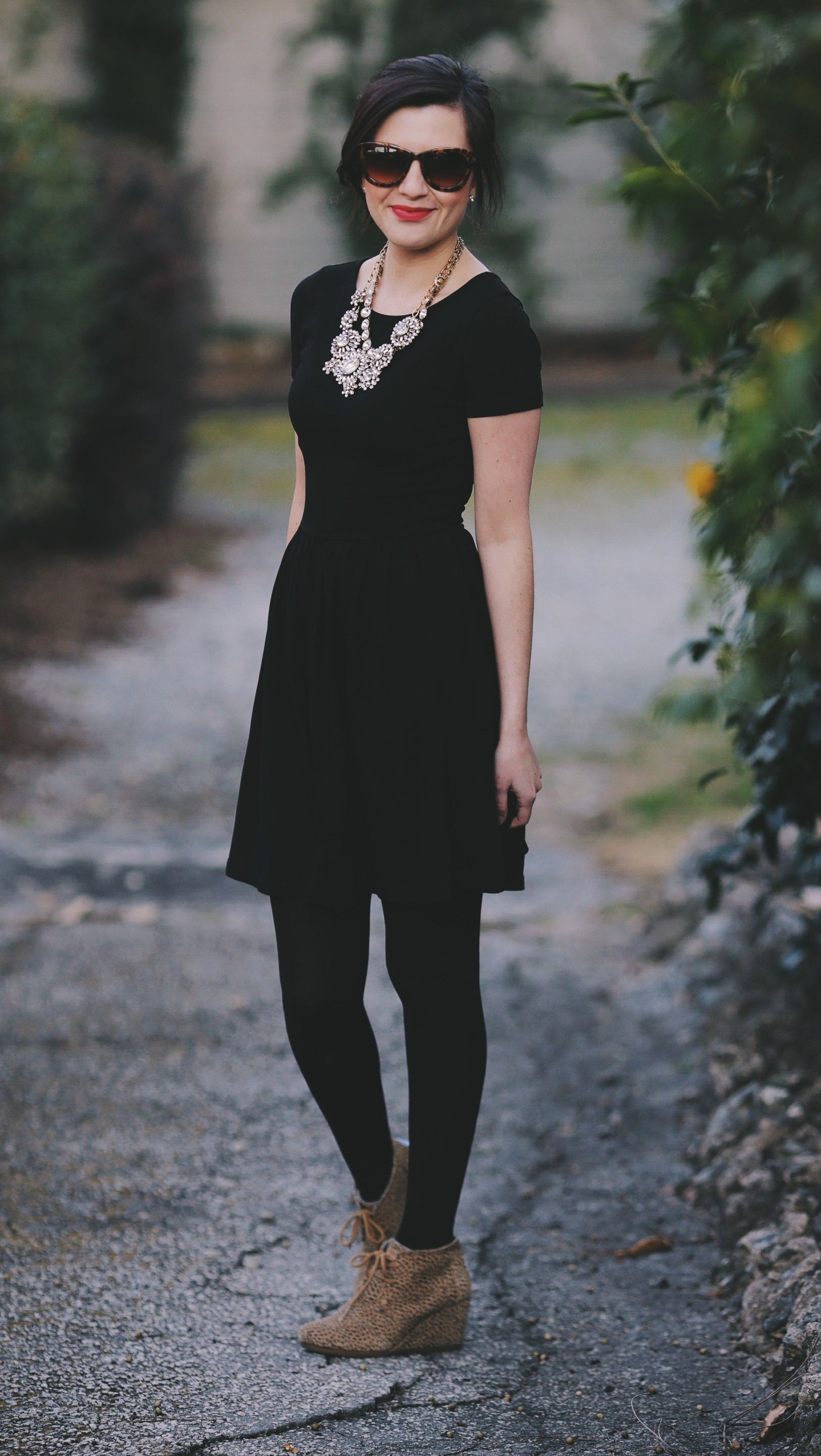 black dress, tights, statement necklace and leopard desert wedges