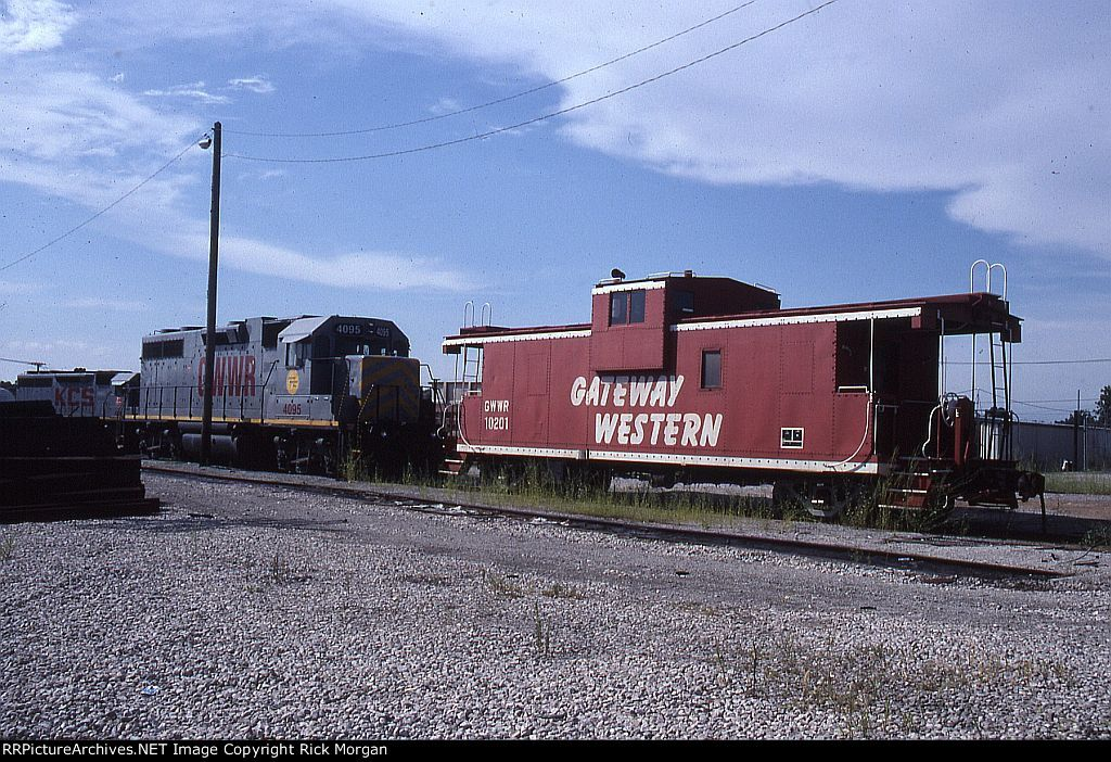 Between Shifts at Mexico   Description:  GWWR power and a caboose lay over in the small yard at Mexico MO between rounds of local duty or a trip down the branch to Fulton.   Photo Date:  8/16/2002  Location:  Mexico, MO   Author:  Rick Morgan  Categories:    Locomotives:  GWWR 4095(GP38-3)