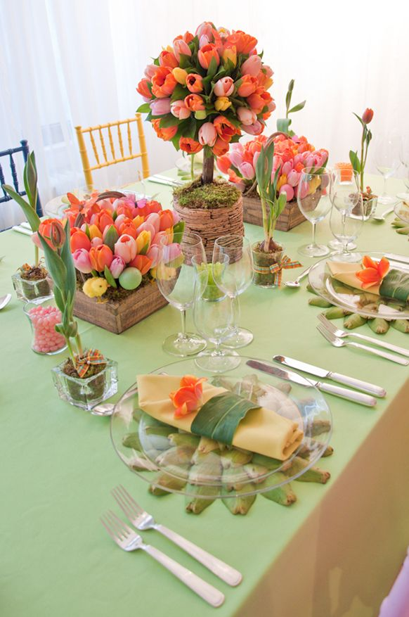 Beautiful spring table... tulips, artichoke leaves under clear glass plates.  Really pretty and sweet.