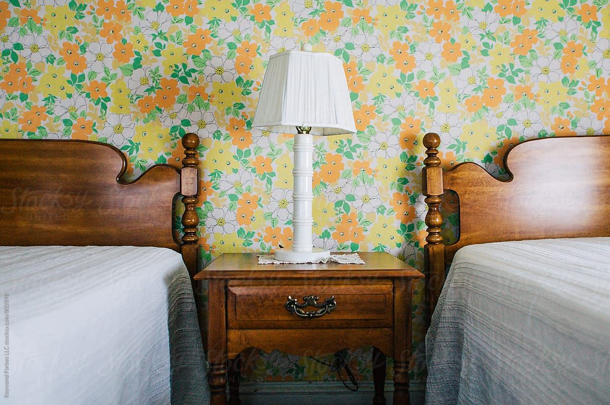 Vintage Motel Room with Wallpaper Lamp and Twin Beds | Stocksy United by Raymond Forbes Photography #stockphoto #stockphotography #wallpaper #vintagewallpaper #niagarafalls #seventies #vintageinteriordesign #bed #nightstand #headboard #vintage