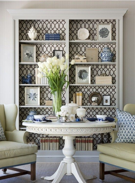 Patterned wallpaper on the back of a bookshelf. have two