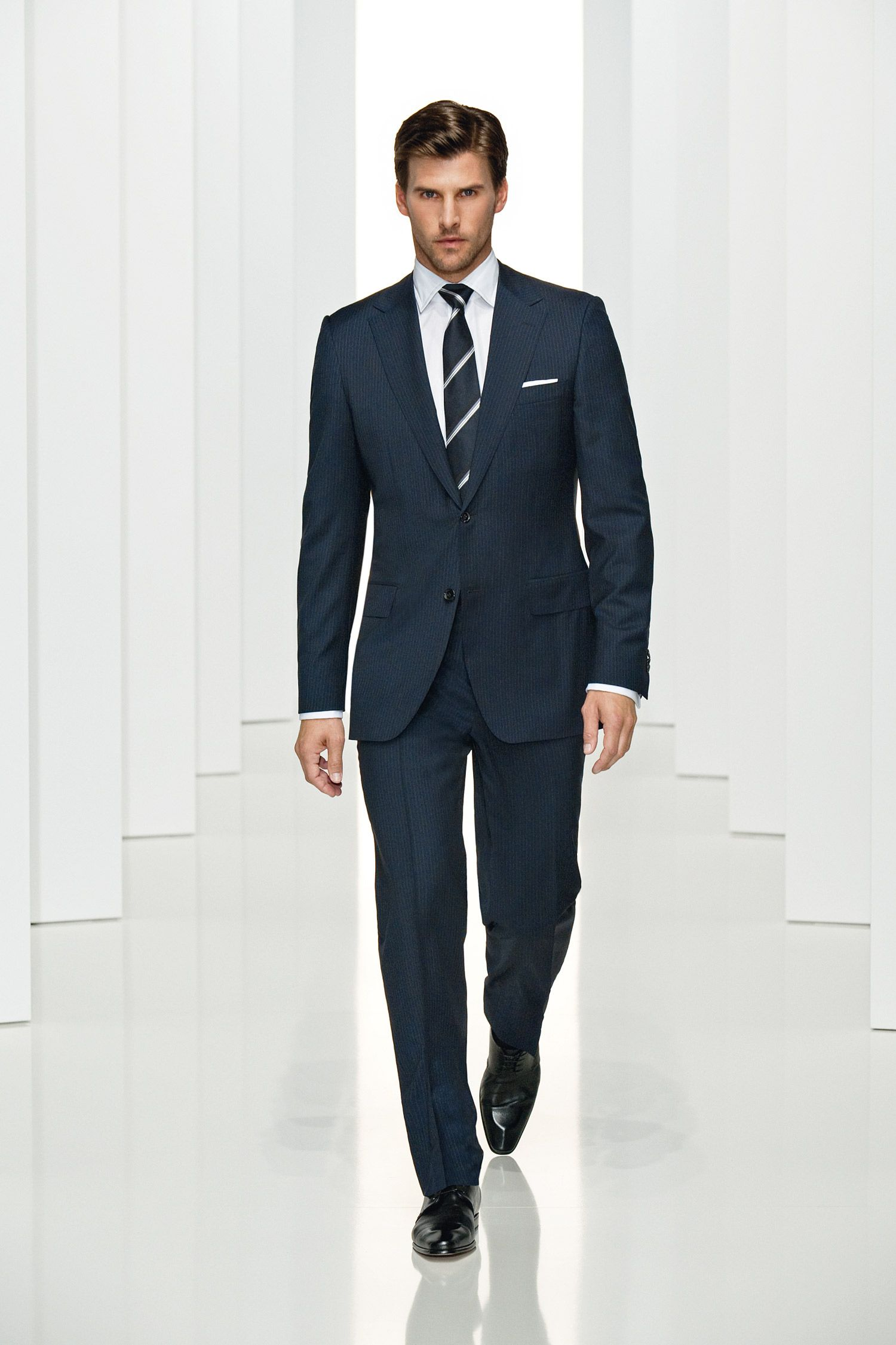 Dark blue suit with white shirt and dark blue and grey stripped tie, white  pocket square