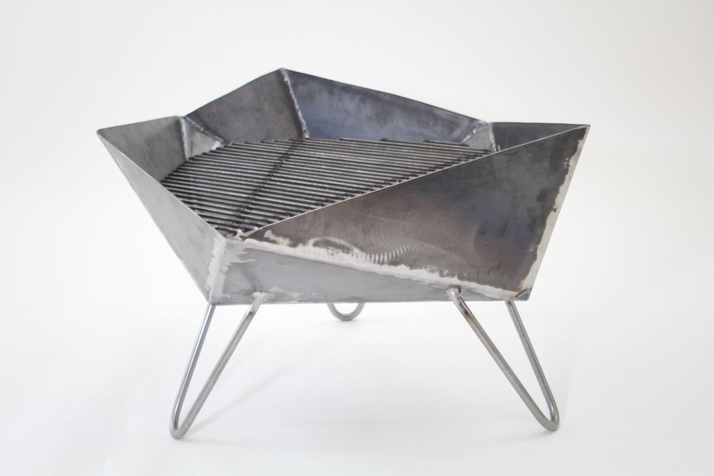 """Only the coolest grill ever!  Grill-meets-sulpture-meets-oragami. This grill is hand made with 1/16""""  thick sheet steel, perched atopthree hairpin legs,and fitted with a  customized cooking surface. It measures 20""""x14""""x14""""h, the perfect size to  take camping or tailgating. When you are done, you can bring your grill  back mess-free since the bottom is completely sealed and won'tleak ashes."""