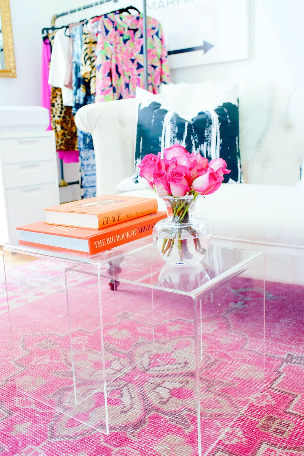 Lucite nesting tables as coffee pink persian rug white sofa orange books and clothing rack also tour the chic home office of house harper   leading lady for