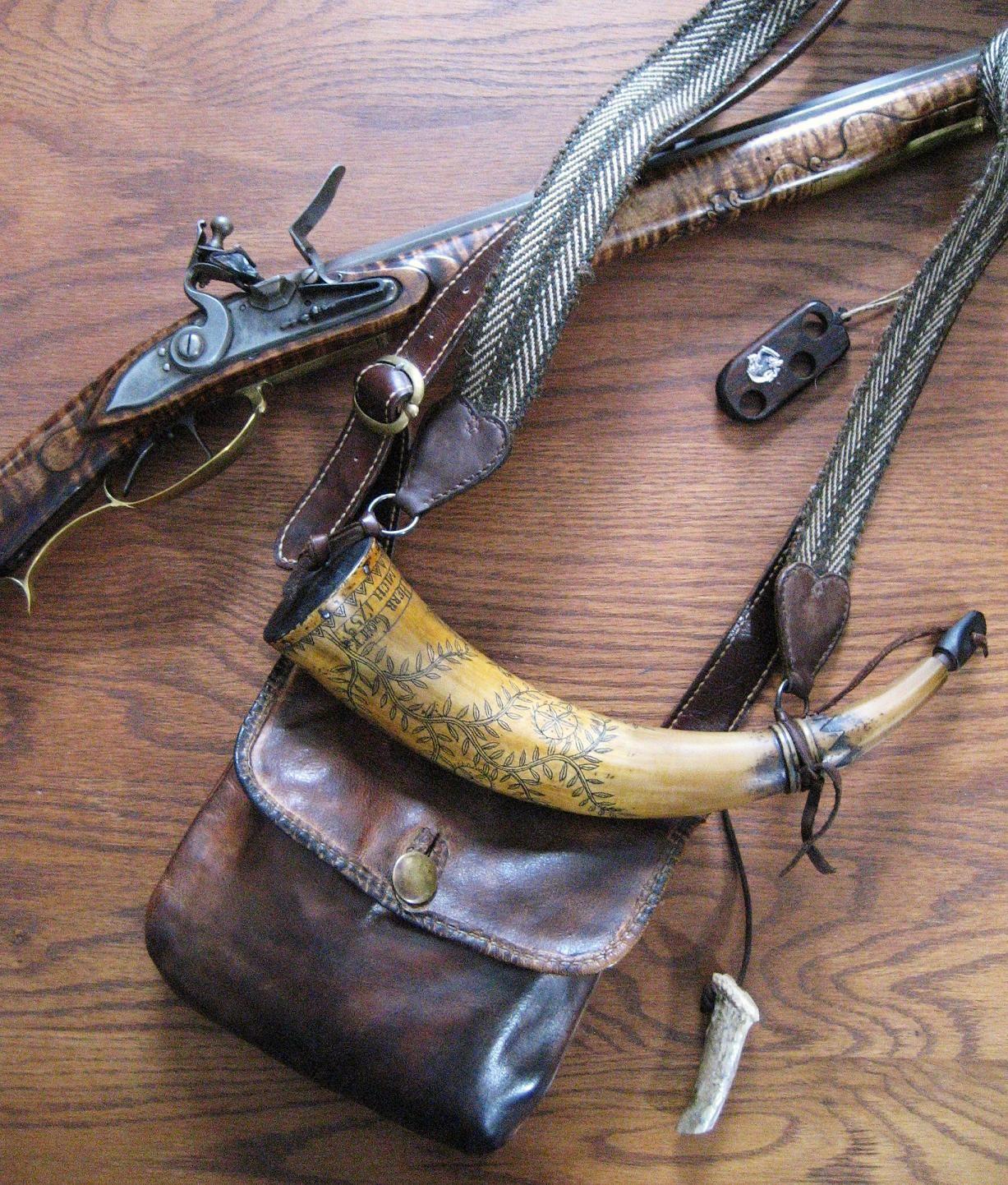 ".50 rifle  Bag & other leather work - Jeanne McDonald  Buckle - Rich McDonald  PA German inscription horn - Mike Hawkins  Linen/wool woven strap - C.J. Wilde  Powder measure - ""Spark"" Mumma  Rifle - R. Thomas Caster"