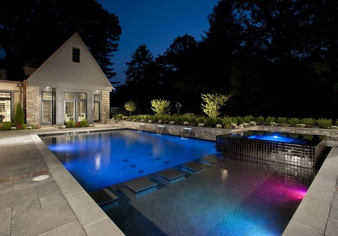 Colorful LED lighting gives this geometric pool and spa an ...