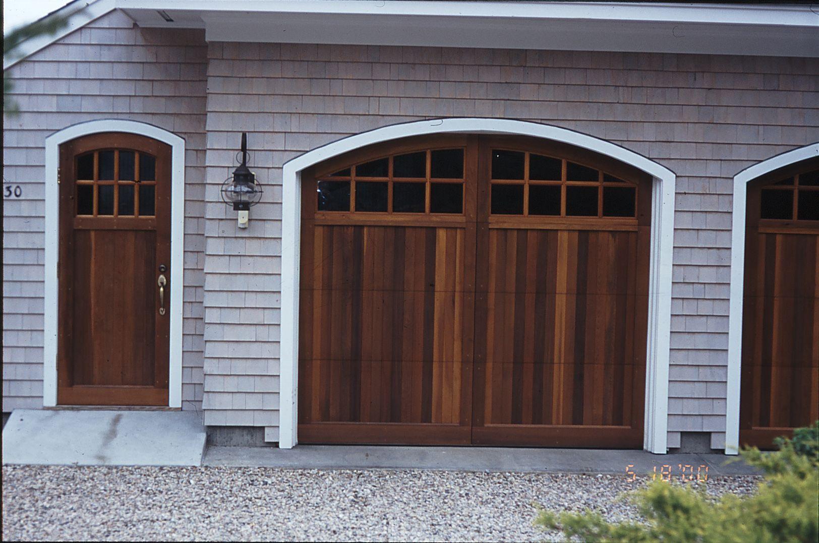 single garage doors with windows. two single garage doors, stained dark, curved top with windows, vertical v- doors windows