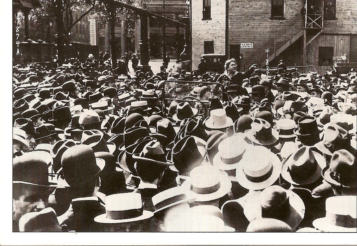 Emma Goldman, preaching to a crowd of men in hats.