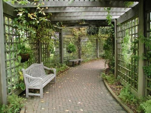 Covered garden walkway with trellis, brick pavers, bench