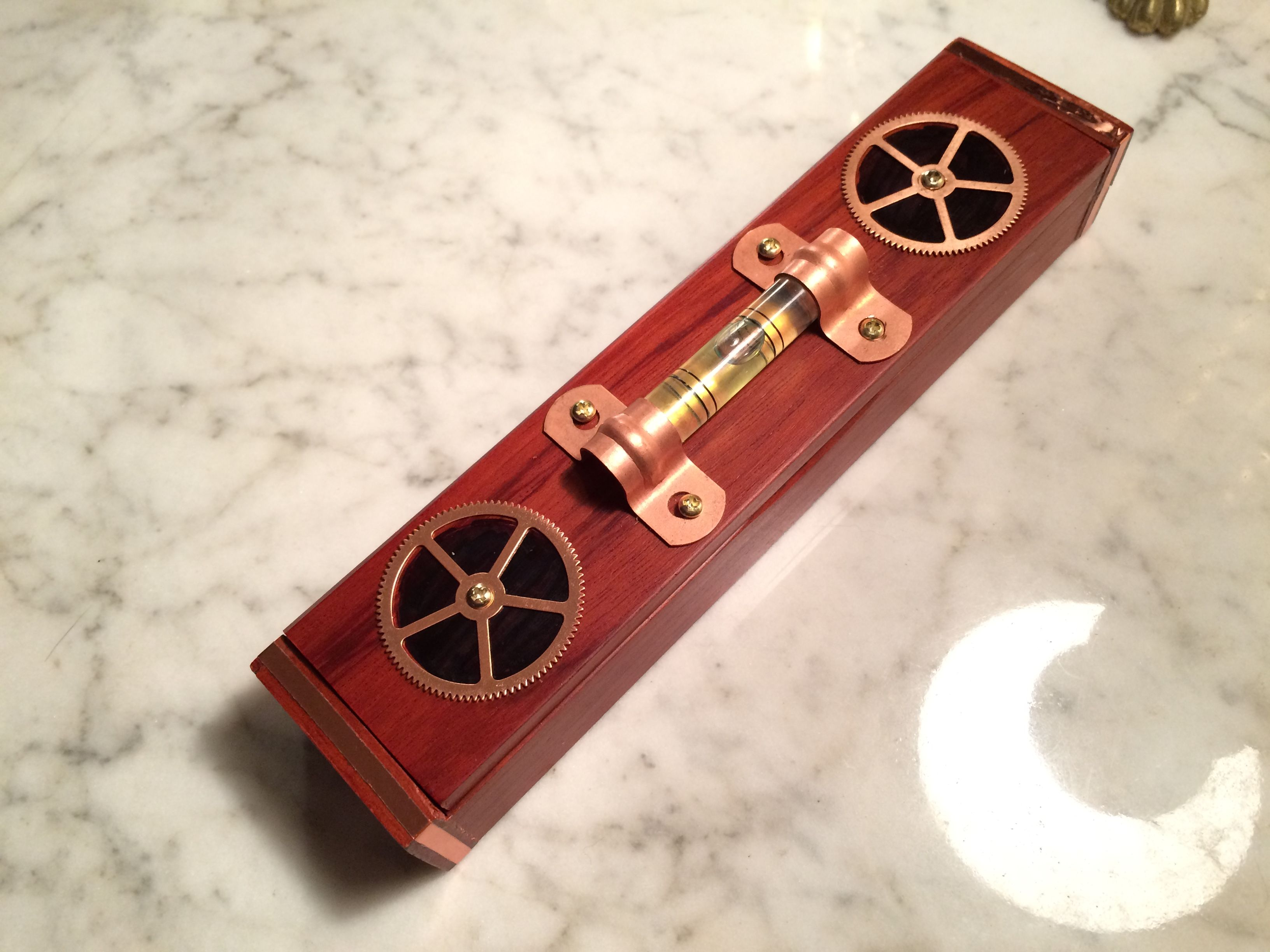 """iGearz Steampunk Pen Box - Copper Level - Here's a nice accessory for your desk, it's an iGearz Steampunk Pen Box. A handsome wood box with a working bubble level and two copper gears on the hinged lid with copper accents. Perfect for storing your favorite pen or pencil, holding paperclips, whatever you want to keep safe and at hand. Use it at your home office, at work, anywhere. (Box is a repurposed """"Tourneau"""" box and that name is now inside the lid.)"""