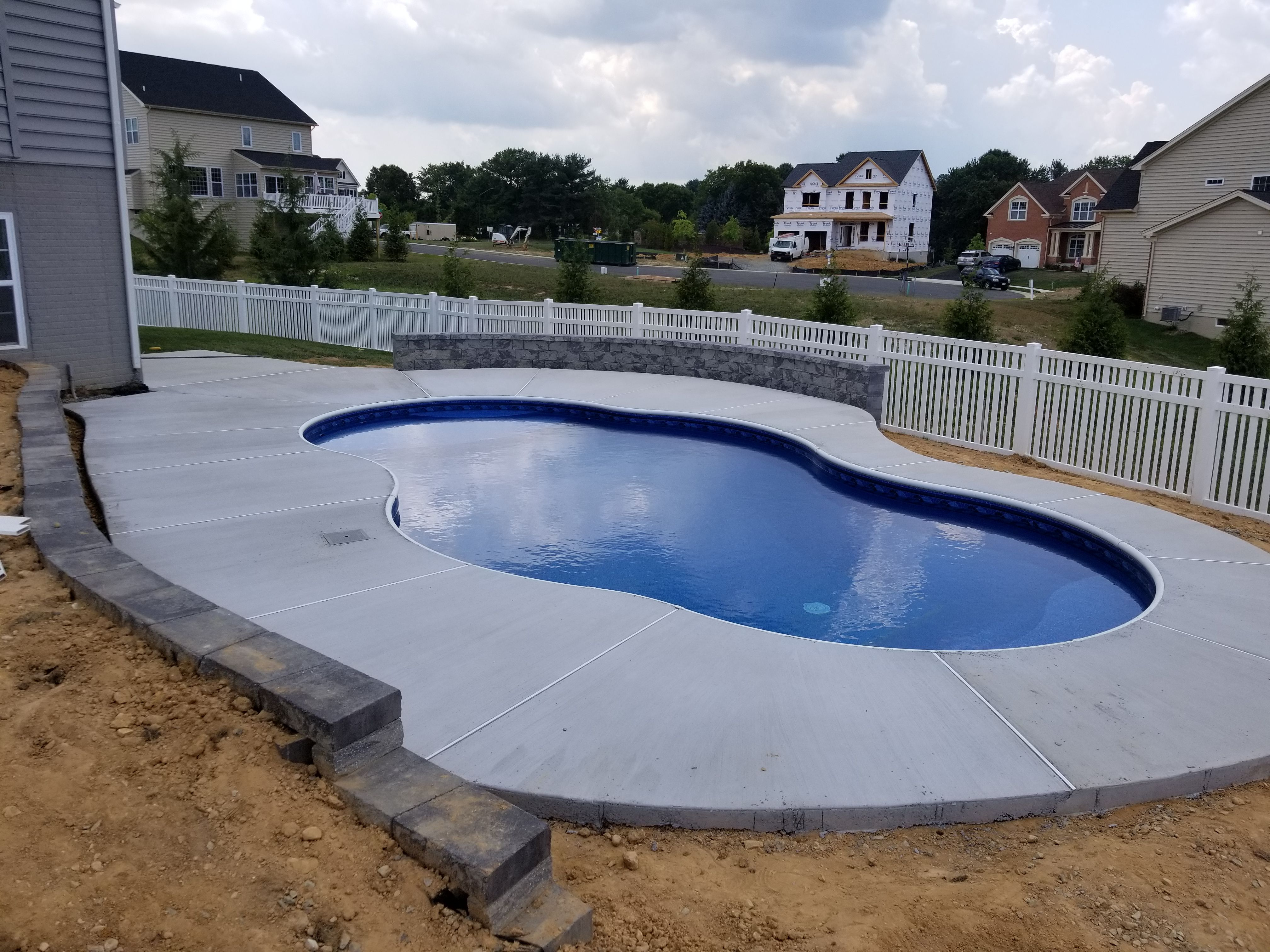 Freeform Pool With Retaining Wall Sitting Wall And Broom Finished Concrete Pool Freeform Pools Retaining Wall
