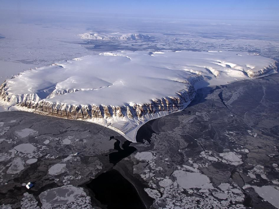 This image of Saunders Island and Wolstenholme Fjord with Kap Atholl in the background was taken during an Operation IceBridge survey flight in April, 2013. Sea ice coverage in the fjord ranges from thicker, white ice seen in the background, to thinner grease ice and leads showing open ocean water in the foreground.