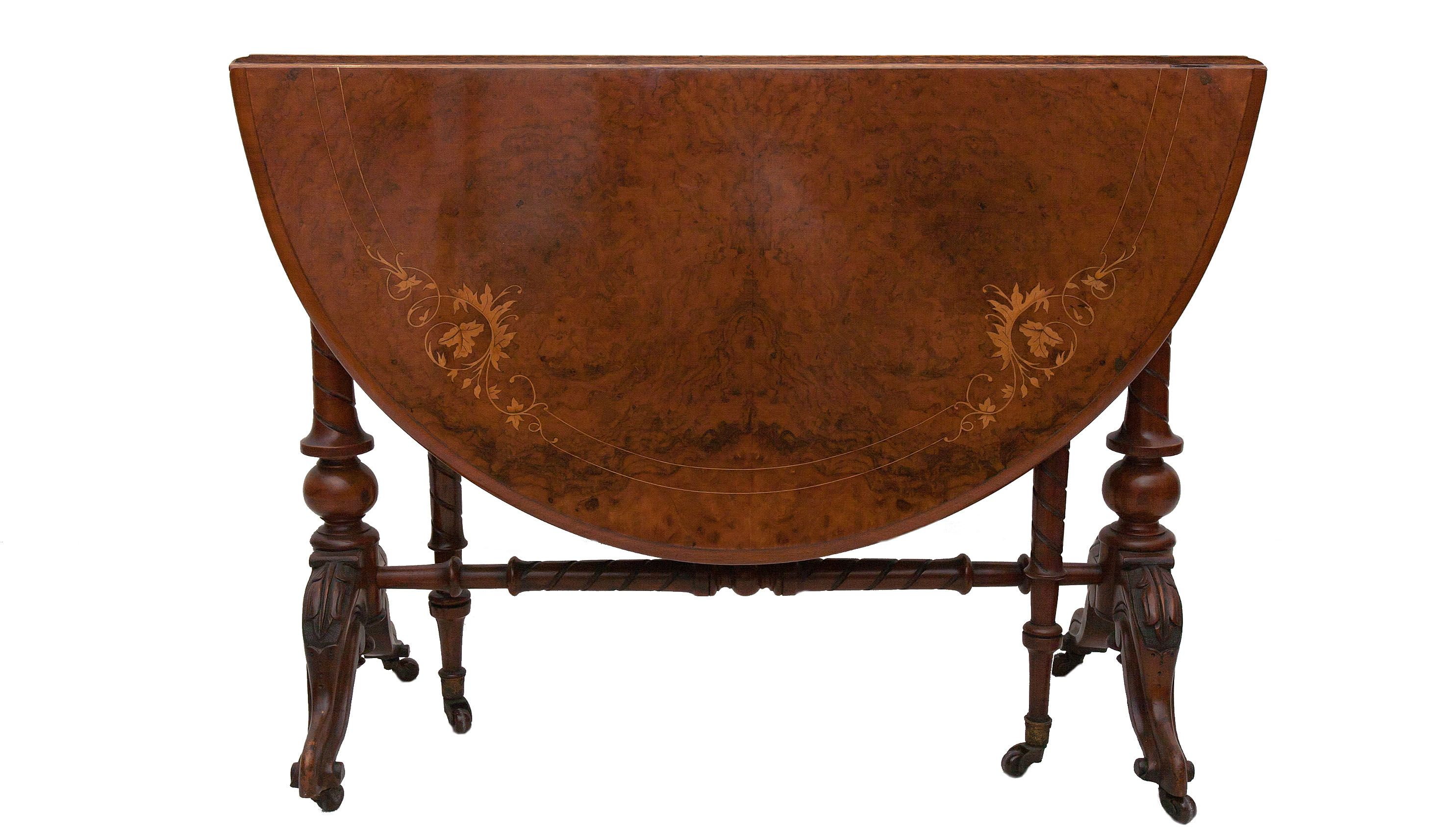 A stunning walnut veneered drop-leaf Sutherland table with beautiful leaf decorative inlay. Exquisitely carved and supported on two columns united with turned stretcher and two swinging legs raised up on brass ceramic cabriole casters.                                    C.1870