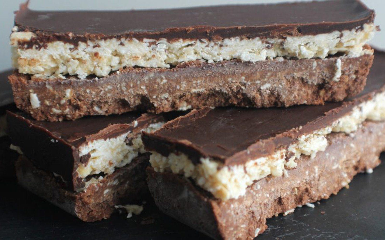 <p>These bars are three layers of elegant bliss. The base is a cocoa nut and seed butter shortbread that is topped with a rich coconut filling and a silky chocolate sauce to finish the whole thing off. </p>
