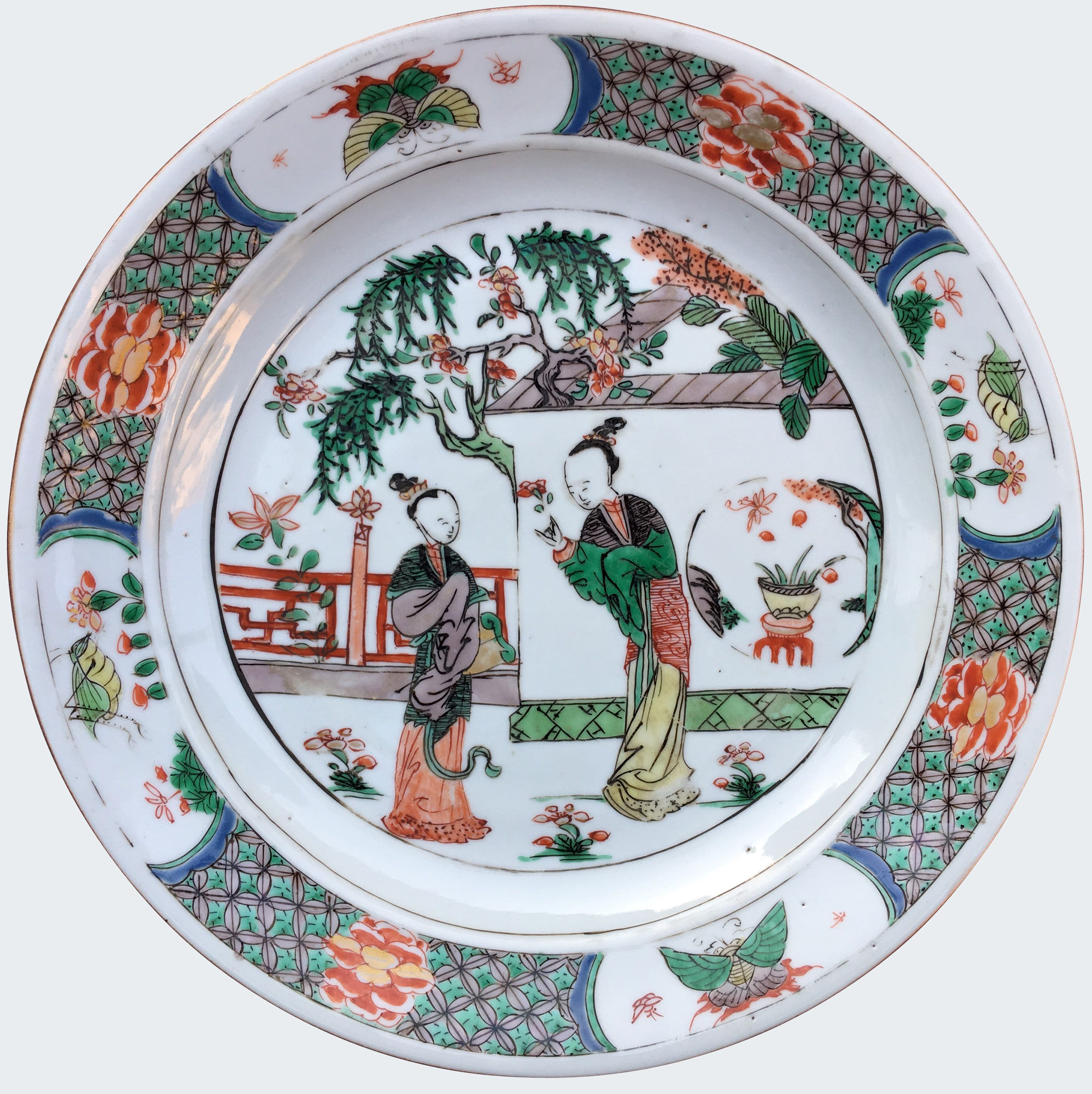 A Chinese export porcelain famille verte plate decorated with figures. Kangxi period. China/Asia. Decorated in the famille verte palette, with two ladies in a fenced garden outside a walled enclosure