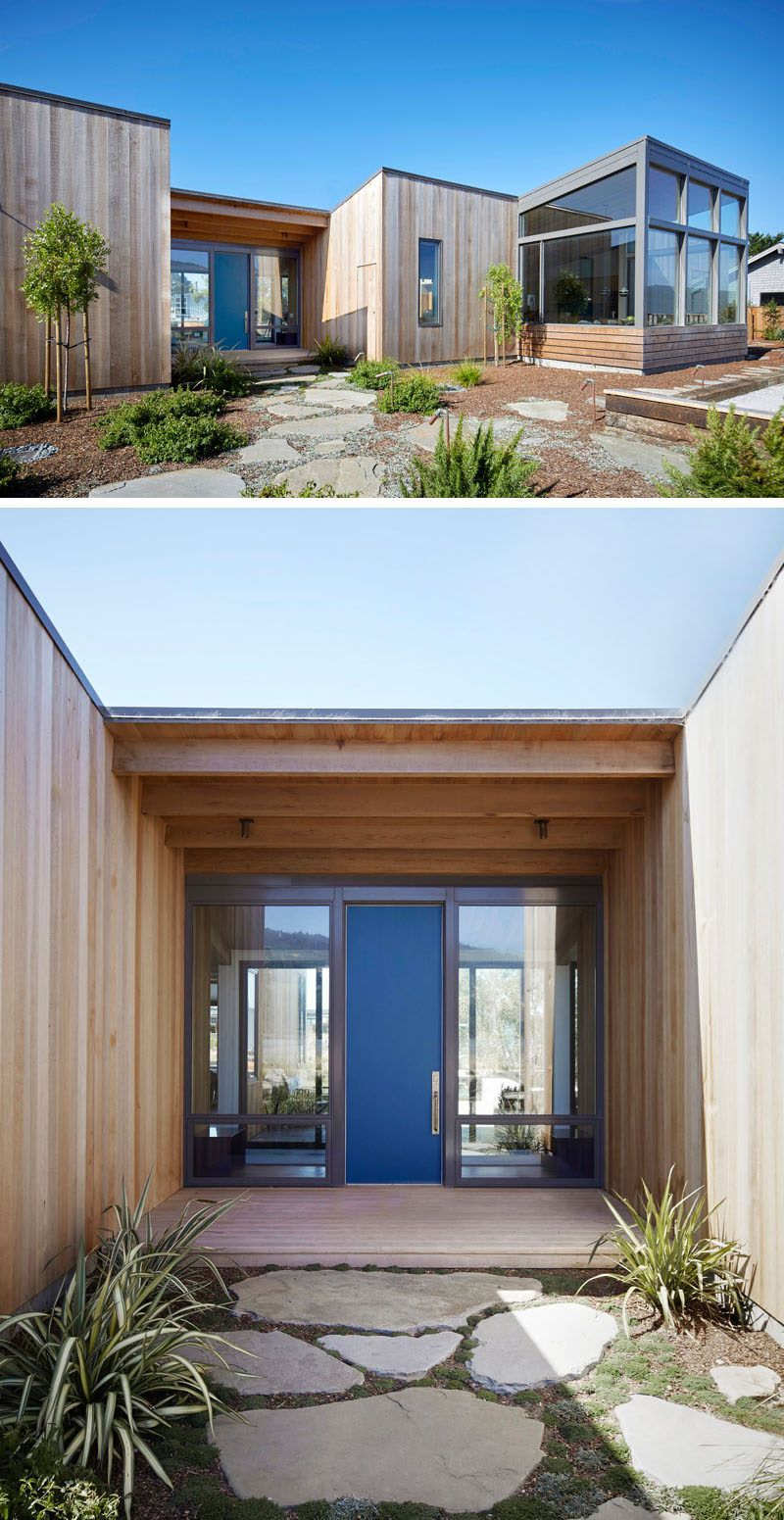 At the front of this house minimal landscaping with stepping stones guides you to the blue front door that adds a pop of color to the home