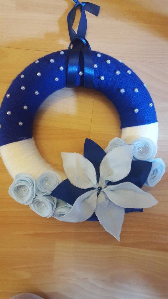 Photo of Christmas outside wreath in white and blue shades in wool and hand-made pannolenci. Christmas garland