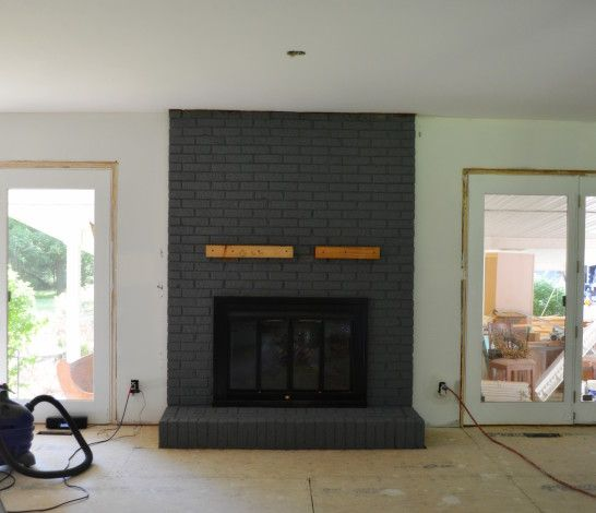 Inspiring Black Brick Fireplace With Double Brown Wooden Mantel Shelf And Black Metal Fire Painted Brick Fireplaces Fireplace Remodel Brick Fireplace Makeover