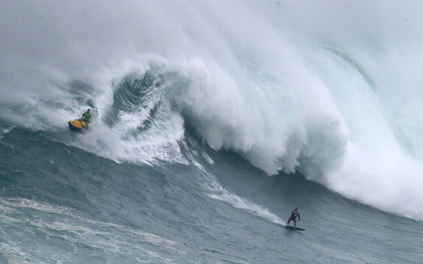 A surfer rides a big wave during a tow-in surfing session at the Praia do Norte, or North beach, in Nazare, Portugal, Sunday, Nov. 1, 2015. US surfer Garrett McNamara set a world record for the largest wave surfed when he rode a 23.7 metre wave (78-foot) in Nazare in 2011. (