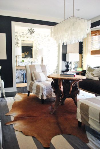 Dramatic Living Room With Capiz Chandelier, Black Walls, White Trim, Cowhide  Rug Over Striped Rug,