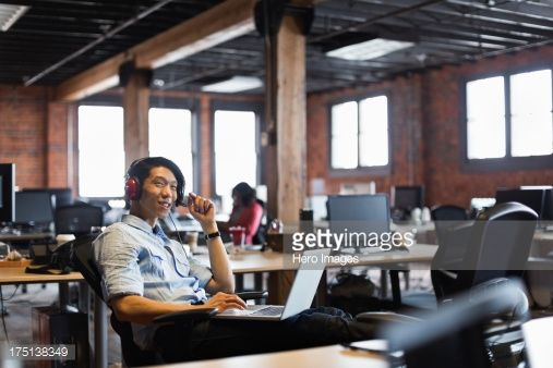 Stock Photo : Smiling entrepreneur working on laptop in creative office space