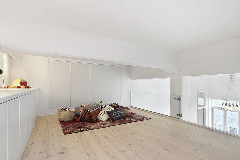 Witte Loft Stockholm : Gezellige mezzanine met bergkasten en zithoek in witte loft