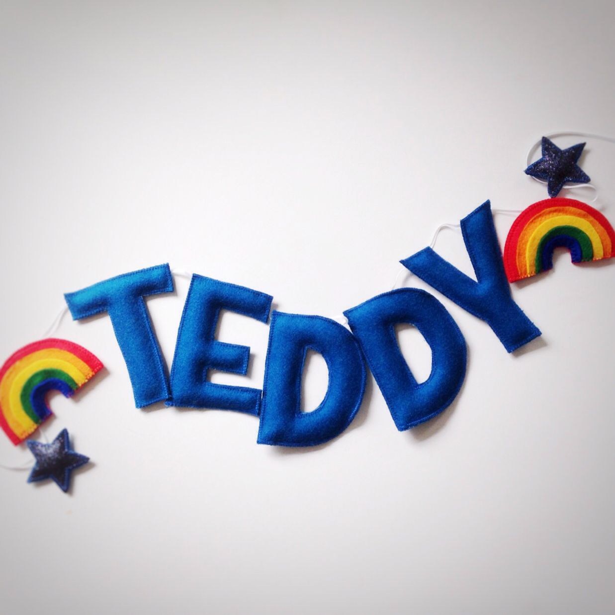 A felt and glitter personalised name garland with rainbows and stars. Bright rainbow colours and teal blue felt, by the secretcrafthouse.com