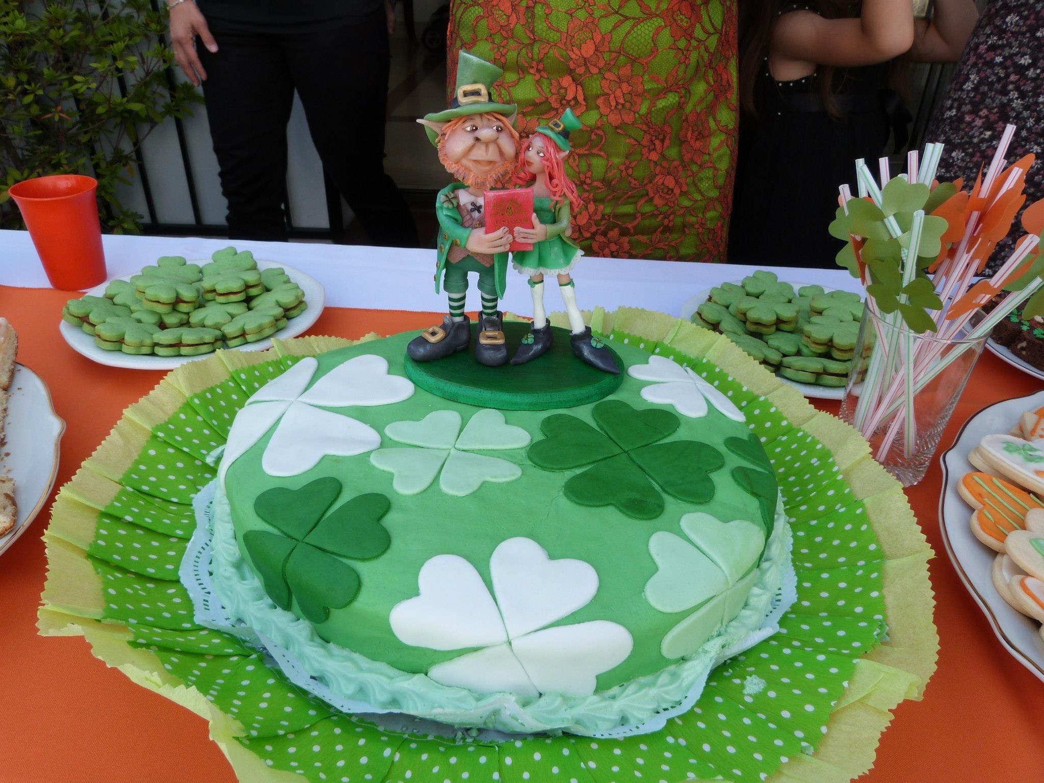 Torta de banana split con decó de tréboles y muñequitos personalizados de duendes irlandeses con libreta de casamiento civil, realizados en porcelana fría,