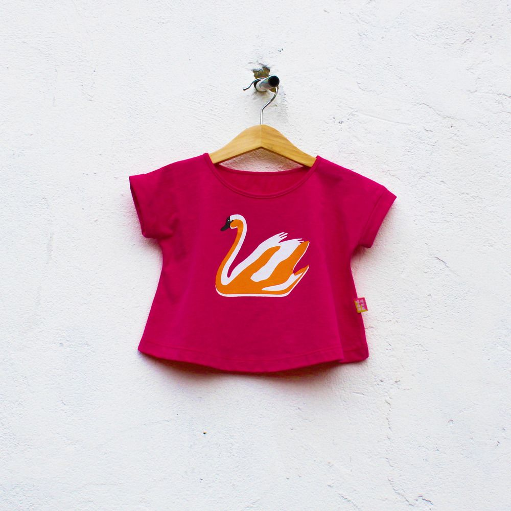 Super soft jersey, 100% cotton tee in strawberry fuchsia colour. Hand silkscreen printed with a swan print. Slightly wider than a regular tee, can be worn as a cropped top when your toddler outgrows it. Designed and produced in London.