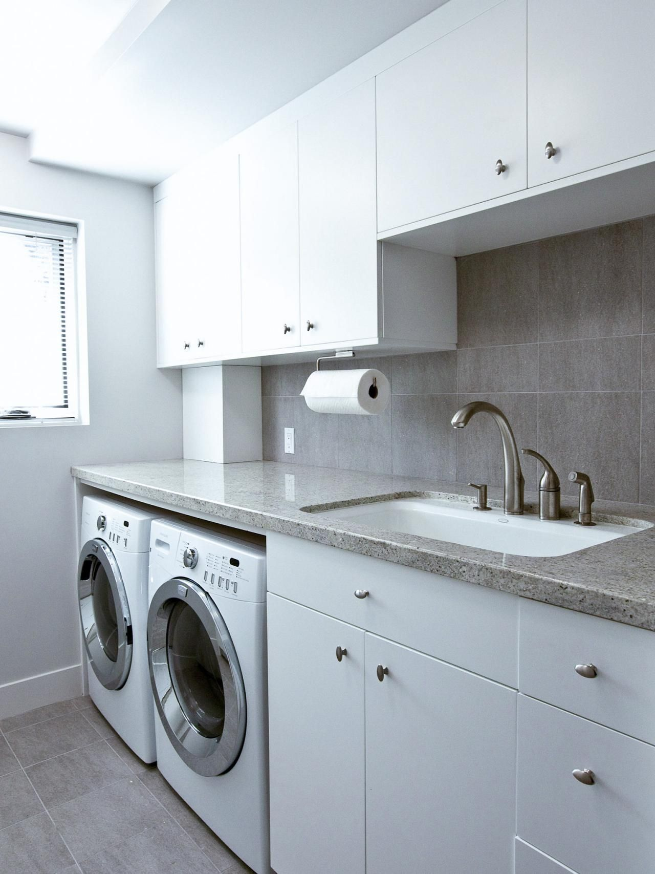 This modern laundry room features a folding counter, sink and plenty ...