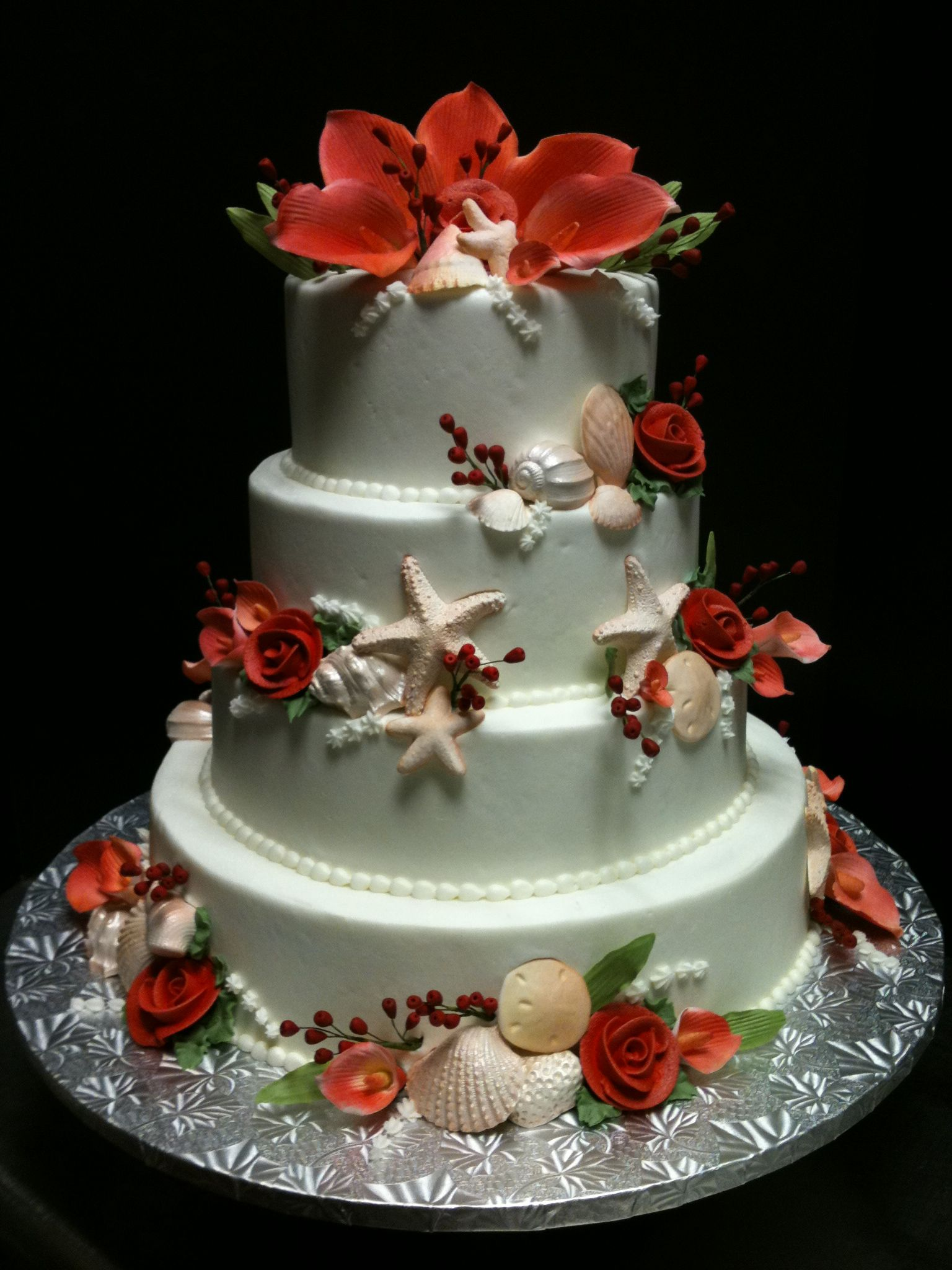 Perfect for the beach loving bride! This wedding cake is covered in exotic flowers in a beautiful coral color, along with starfish and seashells!
