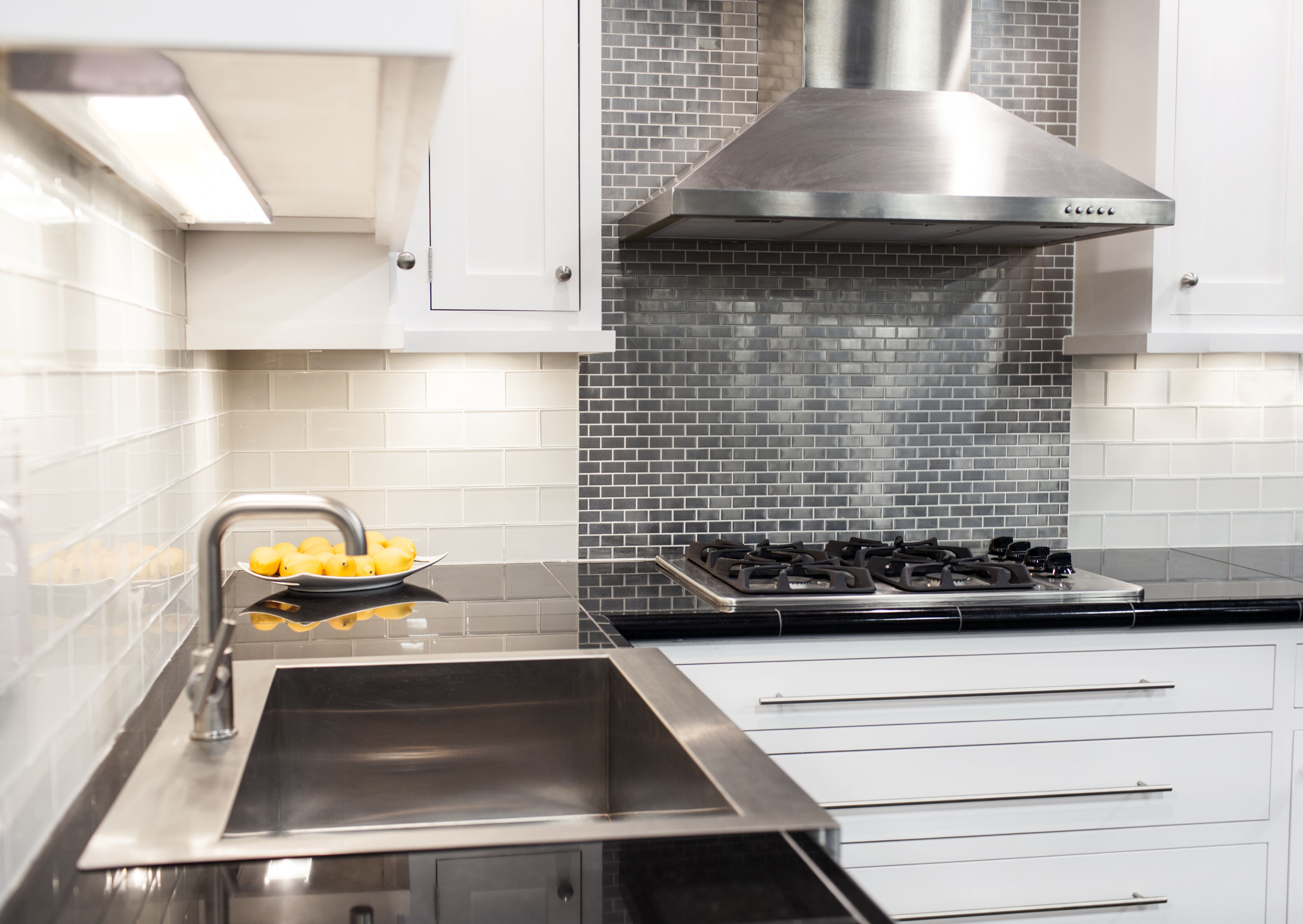Stainless Steel Tile Makes A Great Focal Point Behind The Cooktop Glass Subway And Black Granite Round Out This