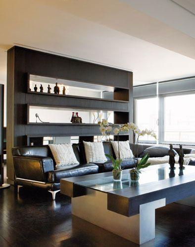 Una viga y una librería, diseño del arquitecto Juan Ybarra, enmarcan la zona de estar: la mesa de centro de Guadarte, y un único sofá, de Balthus