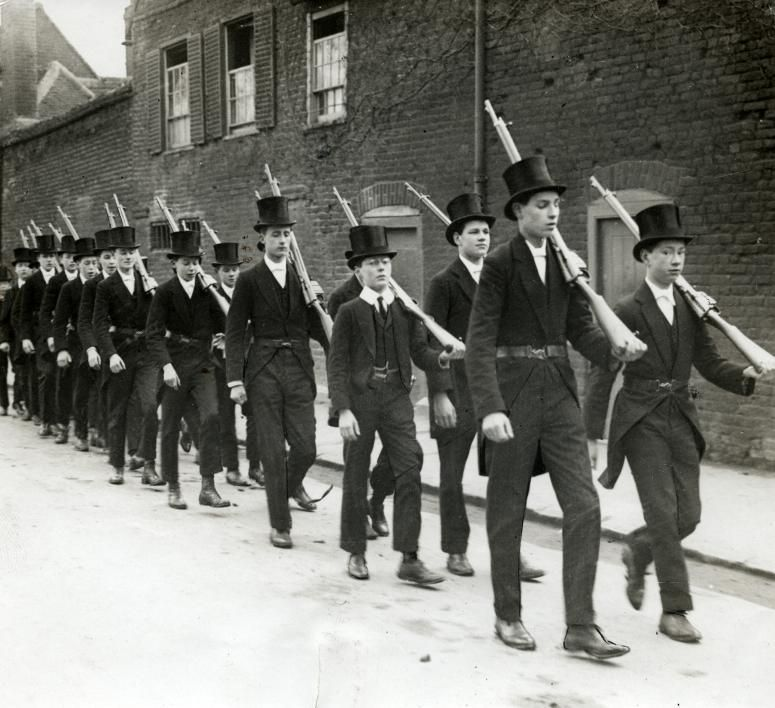 U.K. Pupils of Eton college exercising in suit and high hat, rifle over the shoulder. England, 1915.