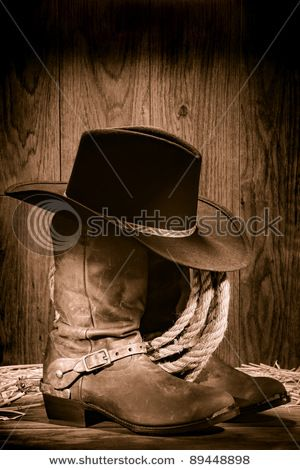 1c1fb5f7b83 American West rodeo cowboy black felt hat atop worn western boots and spurs  with old ranching rope in an antique wood barn in nostalgic vintage sepia